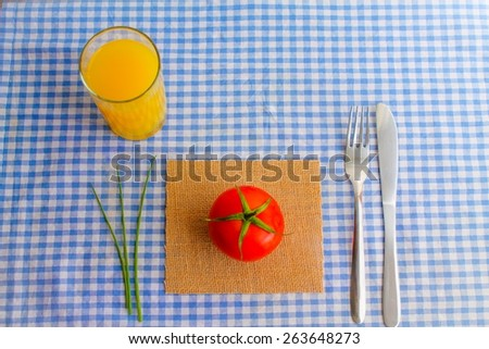 A simple meal - A red raw tomato with chives and cutlery on a blue gingham tablecloth with a glass of orange juice - stock photo