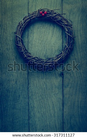 A simple, natural Christmas wreath woven from soft twigs with artificial red berries,  on an old, weathered oak wood plank door.  Cross processed with vignette added to give vintage or retro effect. - stock photo