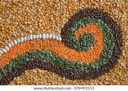 A simple pattern of a fern leaf or swirl made from split peas, lentils, and white beans. Nice harvest and autumn colors. A bold design that can be used as a horizontal, vertical or flipped format.  - stock photo