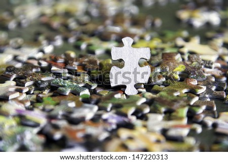 a single blank piece of jigsaw within a whole jumble of puzzle pieces - stock photo