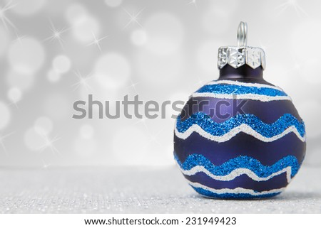 A single blue ornament on a glittery sparkling table - stock photo