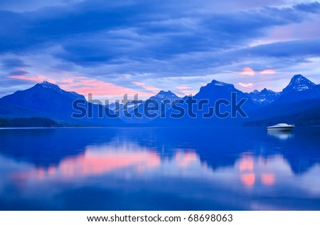 A single boat rests on a calm Lake McDonald surrounded by beautiful sunrise color. - stock photo