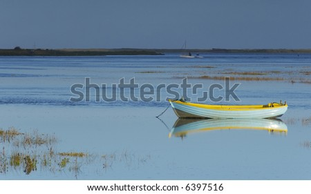 A single boat with a yellow stripe on the Burham Deepdale Marshes - stock photo