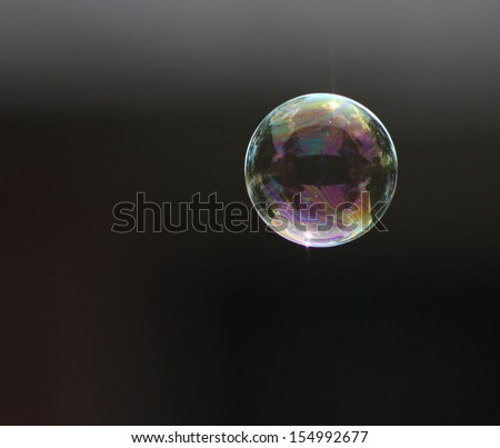 A single bubble floating over a dark background - stock photo