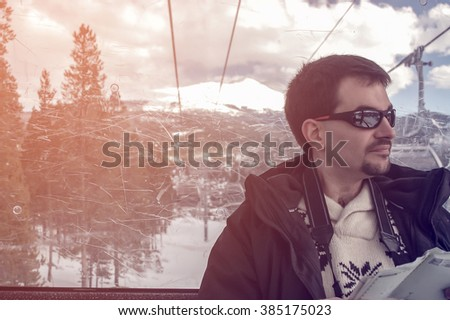 A single caucasian man traveling with a digital camera  and map sitting on a cable car in winter with snow covered mountain background at Colorado USA, vintage filtered tone. - stock photo