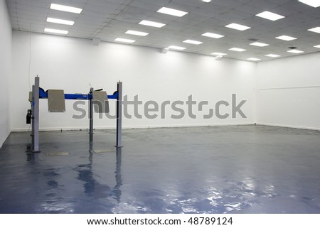 a single lift in car service garage with a blue floor (equipment for diagnostics of car) - stock photo