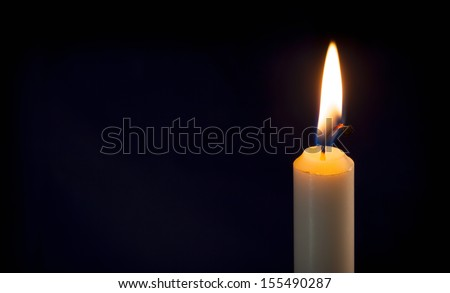 A single lit candle on a dark background. - stock photo