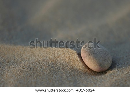 A single pebble at the beach creating a peaceful scene - stock photo
