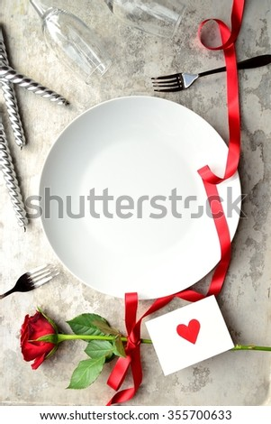 A single red rose,red heart message card and white dish.Image of dinner on Valentines day - stock photo