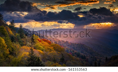 A single shaft of golden dawn sunlight illuminates autumnal ridges and valleys in Great Smoky Mountains National Park - stock photo