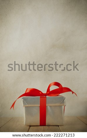 A single silver Christmas gift box, tied to a bow with red satin ribbon, on an old wood plank table with parchment background.  Vintage style. - stock photo