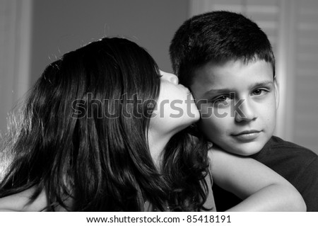 a sister giving her brother a kiss on the cheek. - stock photo