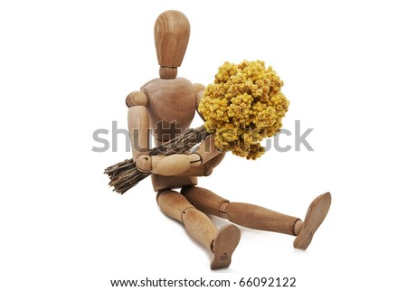 a sitting wooden mannequin with a bunch of immortelle flowers - stock photo