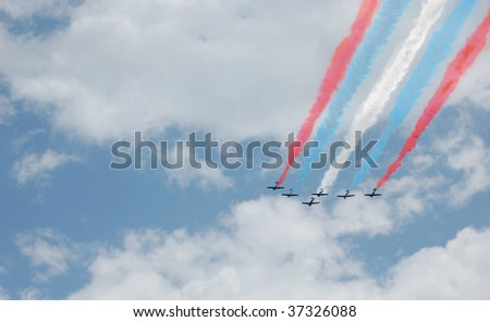 A six plane formation with red, white, and blue smoke trails - stock photo