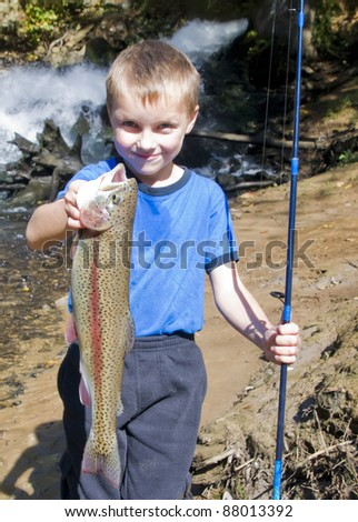 A six year old kid with a big rainbow trout - stock photo