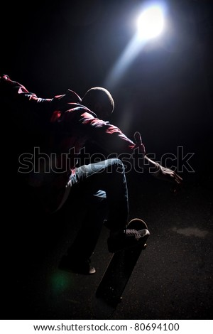 A skateboarder performs tricks under dramatic rim lighting with lens flare. Shallow depth of field. - stock photo