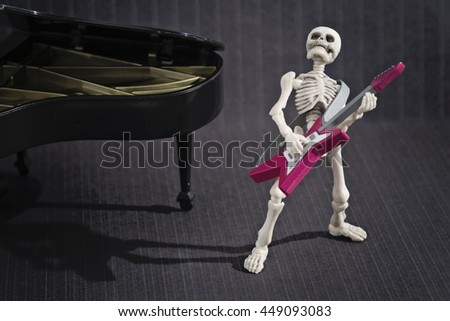 A Skeleton playing electric guitar - stock photo