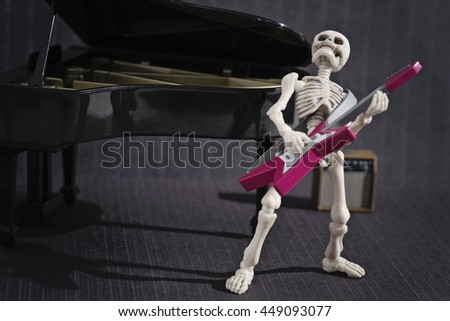 A Skeleton poses with his electric guitar - stock photo