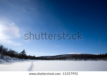 A ski trail going accross a frozen lake infront of a mountain landscape - stock photo
