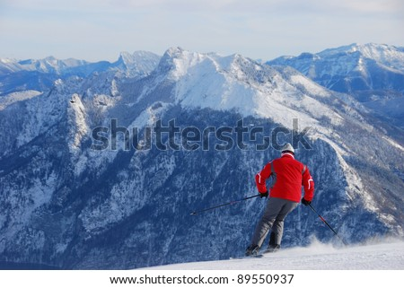 A skier in red jacket ski cross the slope with snowy mountains as background - stock photo