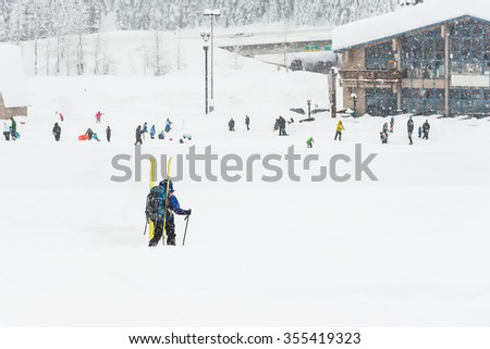 a skier walking on snow with ski board on the back,scenic view of small people  around ski resort when snowy day. - stock photo