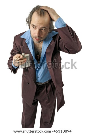 A sleazy car salesman, Con man, retro suit wearing cool guy with worried facial expression drinking from a flask and smoking. - stock photo