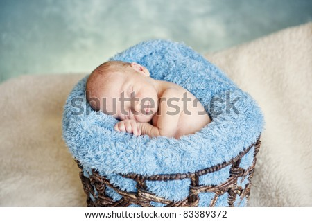 A sleeping newborn baby boy with focus on his face - stock photo
