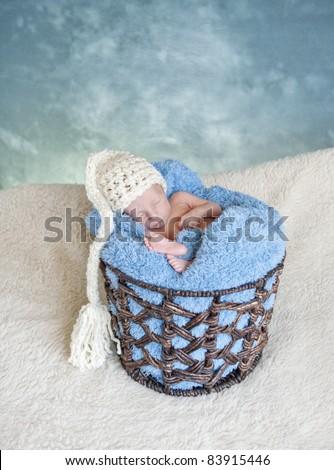 A sleeping preemie newborn baby boy wearing a hat in a basket, studio shot - stock photo