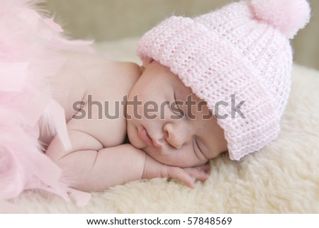 A sleeping three week old baby girl wearing pink hat  with soft focus - stock photo