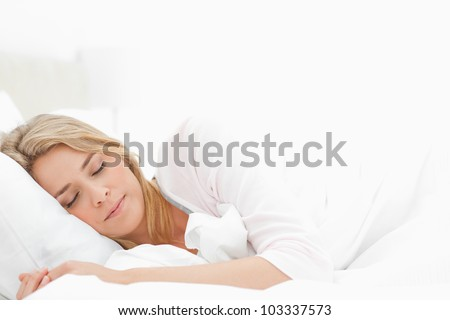 A sleeping woman with her arms stretched slightly out in front of her. - stock photo