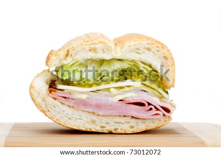 A slice of a Cuban sandwich with pickles, lettuce, spicy mayonnaise, cheese and meat. - stock photo