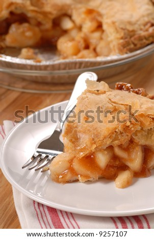 A slice of a deep dish apple pie with a flaky crust - stock photo