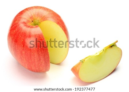 A slice of apple cut out and laying beside it. - stock photo