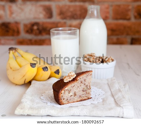 A slice of banana bread with milk, bananas, walnuts on a brick wall background - stock photo