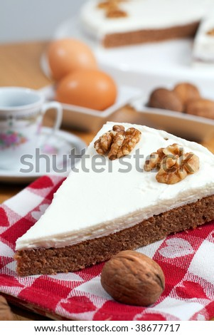A slice of coffee and walnuts cake laid on a towel, surrounded by the ingredients on a wooden table - stock photo
