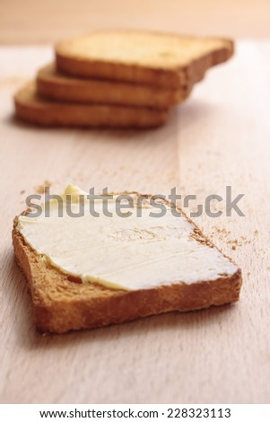A slice of melba toast and thick butter with a small stack in the background on a wooden board - stock photo