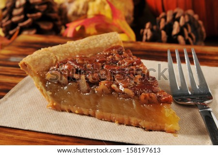 A slice of pecan pie with a festive autumn, Thanksgiving background - stock photo