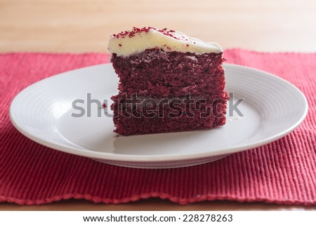 A slice of red velvet cake upright on a white plate - stock photo