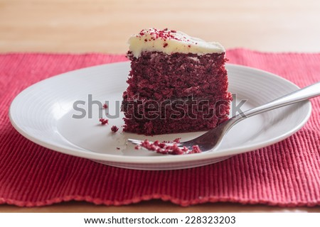 A slice of red velvet cake with a piece missing on a white plate with a fork - stock photo