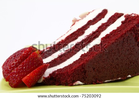 A slice of red velvet cake with white frosting is garnished with strawberries and placed on a square, green plate; close up; white background; - stock photo