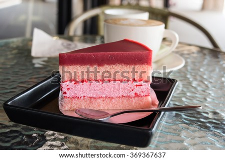 A slice of strawberry mousse cake on a square black tray with a cup of hot latte and glass table  - stock photo