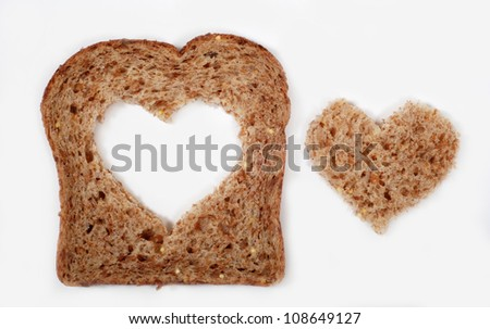 A slice of whole wheat bread with a heart shape cut from the center - stock photo