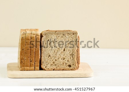 A sliced loaf of sprouted grain and seed bread on a cutting board. - stock photo