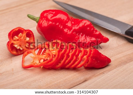 a sliced super hot ghost chili pepper on a wooden cutting board. - stock photo