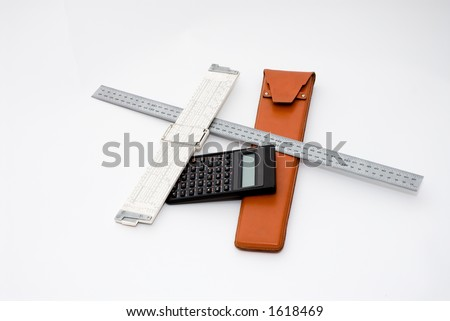 A slide rule and case along with a calculator and a metric ruler against a white background. - stock photo