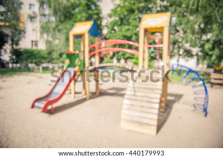 A slider located on the sand in summer. Defocused and blurred image for background of playground, activities at public park. Child swings on modern Colorful kids playground on yard in the park - stock photo
