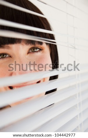 A slightly opened set of blinds with a woman looking through them - stock photo