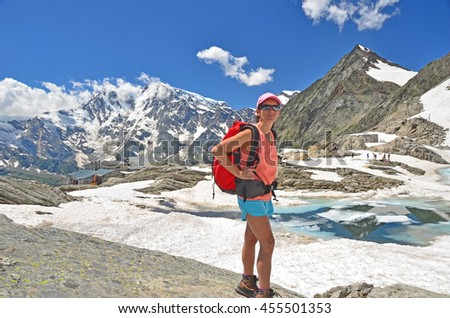 A slim girl hiker high in the Italian alps above an ice covered lake, and with the Monte Rosa in the background - stock photo