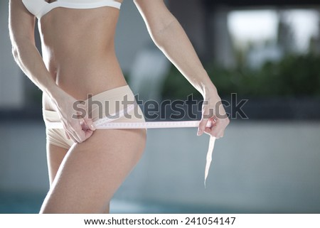 A slim girl measuring her waist, closeup - stock photo
