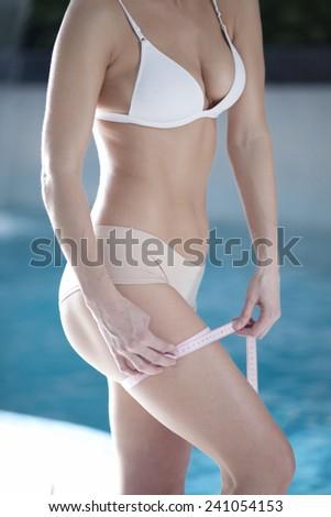 A slim girl measuring her waist, closeup - stock photo